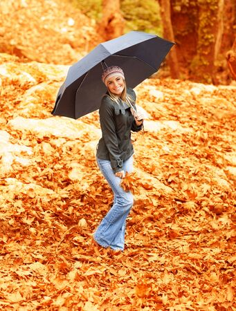 Picture of attractive woman walking under umbrella in rainy day in autumnal park, autumn weather, casual warm clothes, smiling girl hold in hand bouqet of orange dry leaves, beautiful fall season Stock Photo - 16010542