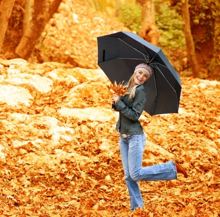 Image of happy female walking under umbrella in rainy day in autumnal park, cheerful blond girl in stylish hat dancing with black parasol in fall forest, usual autumn weather, spend time outdoor  photo