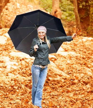 Photo lovely woman walk under umbrella in rainy day in autumnal park, smiling girl hold in hand bouquet of orange dry leaves, cheerful blond model in stylish hat with black parasol in fall forest  photo