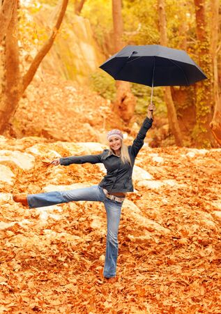 Picture of sweet girl jumping with umbrella in autumnal park, cute blond woman having fun outdoors, pretty female under parasol in rainy weather, fall forest, autumn season, fun and joy concept photo