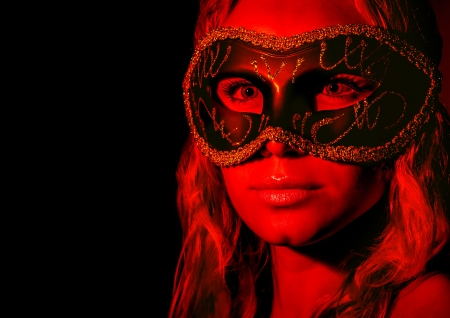 Mysterious woman wearing decorative face mask, girl at holiday party celebration, sexy female in red light isolated on black background, New Year and Christmas fashion costume photo