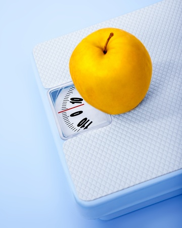 Apple on scale, body weight watching, conceptual image of dieting, calorie count, healthy lifestyle and shape control  photo