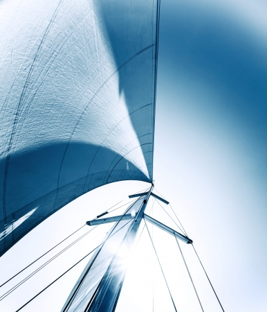 Sailboat in action, big white sail raised over blue clear sky, luxury leisure, summertime activities and extreme sport, boat parts with sun rays, sailing trip vacation, freedom concept Stock Photo