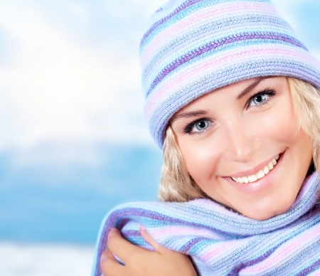 knit cap: Photo of cute blond girl wearing blue warm beanie and scarf Stock Photo