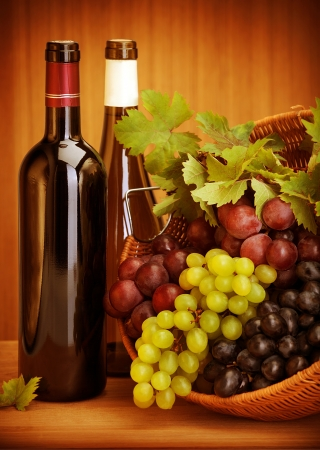 Photo of grape wine still life, two bottle of vine and basket with different kind of grapes on wooden table, alcohol beverage, fresh juicy fruits, winery restaurant, harvest season, luxury concept photo