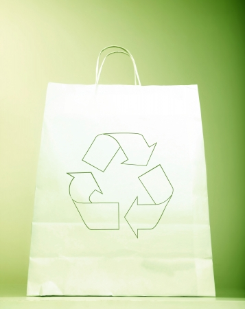 White paper bag with ecology symbol, present with recycle sign isolated on green background, recyclable shopping bag & Eco icon, concept idea to help to save planet  earth from pollution photo