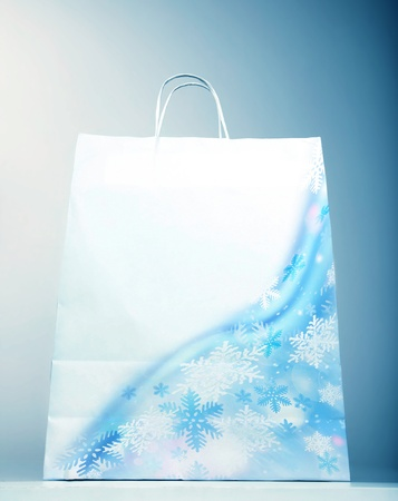 christmastime: Picture of white paper bag with beautiful snowflake isolated on blue background, christmas sale, christmastime shopping, winter purchase, decorative packing new year gifts, holiday packaging  Stock Photo