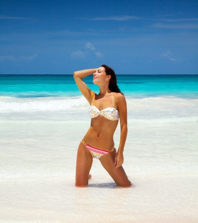 bikini island: Photo of sexy woman on sea side, slim tanned model posing on the beach, attractive woman wearing stylish colorful swimsuit, summer holiday, luxury tropical resort, vacation and travel concept Stock Photo