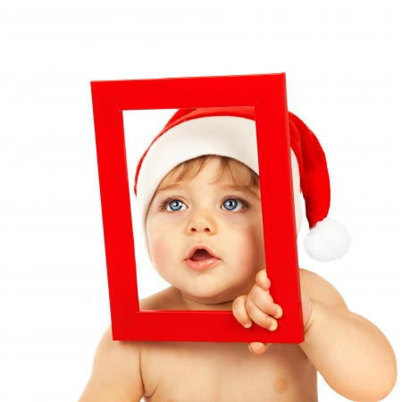 Picture of cute infant looking through red Christmas frame isolated on white background, little boy dressed in pretty Santa Claus hat, winter holidays, xmas celebration, New Year eve, happy childhood Stock Photo - 16367627