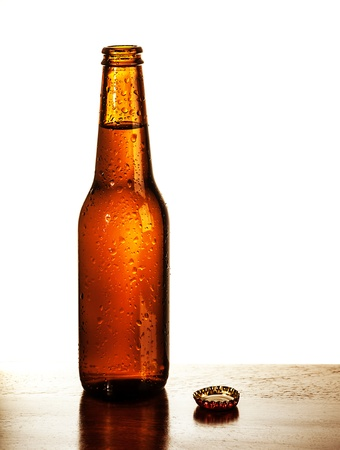 Photo of open beer glass bottle with lid on the table isolated on white background