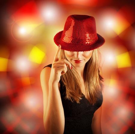 Foto de una mujer rubia vestida elegante sombrero rojo brillante, niña glamour cantante con el dedo hacia arriba aislados en fondo borroso luces, celebración del Año Nuevo, víspera de Navidad, la vida nocturna, club de baile fiesta