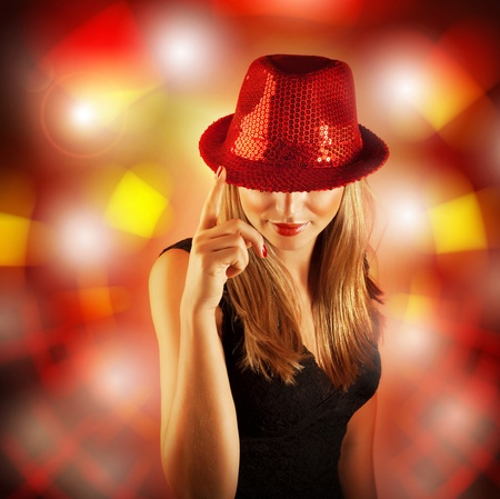 night life: Photo of blond woman wearing stylish shiny red hat, glamour singer girl with finger up isolated on blur lights background, New Year celebration, Christmas eve, night life, dance club party