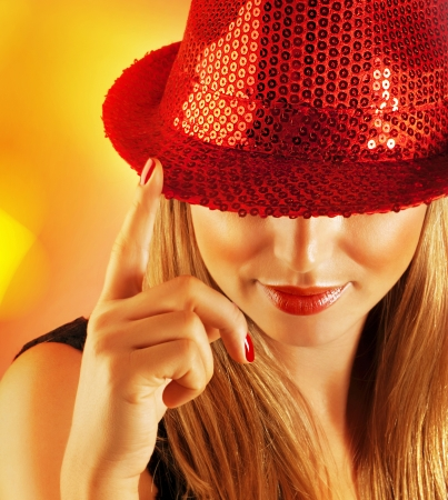 rhinestones: Picture of of luxury singer girl isolated on yellow blur background, closeup portrait of pretty woman wearing stylish red hat which covered her eyes, Christmas holiday, New Year party, night lifestyle Stock Photo