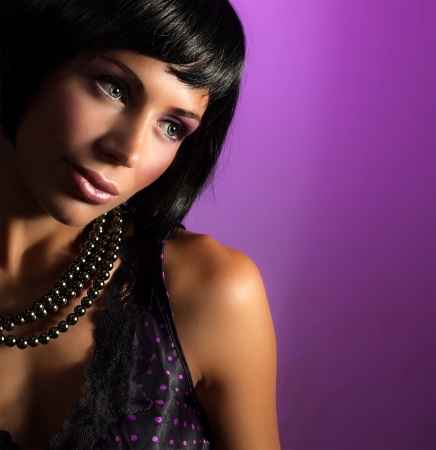 sexy black dress: Photo of beautiful woman with black pearl isolated on purple background, attractive brunet girl wearing glamorous accessories, New Year holiday celebration, stylish hairstyle, luxury makeup