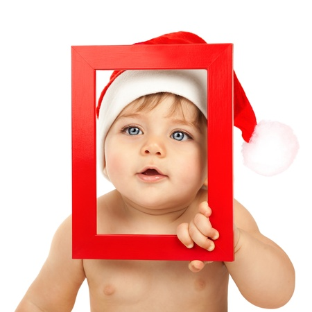 Photo of cute baby boy wearing Santa Claus hat, closeup portrait of curious infant looking through red Christmas frame isolated on white background, happy childhood, winter holidays, New Year eve photo