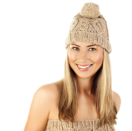 Picture of blond woman wearing beige stylish warm hat, closeup portrait of pretty girl in fashionable winter cap with fluffy bubo isolated on white background, Christmas style, New Year fashion photo