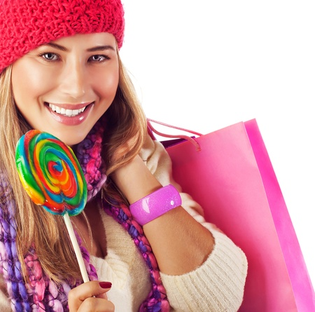 Image of nice blond girl wearing warm winter red hat and eating tasty sugar candy, sweets shop, Christmas present bag, stylish accessories, New Year goody-goody, christmastime holidays photo