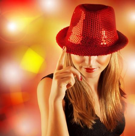 Obrázek krásná žena na sobě Red Hat vztahuje lesklé kamínky a zpívá na jevišti v módní klubu, blond dívka na barevné pozadí zářící, vánoční večírek