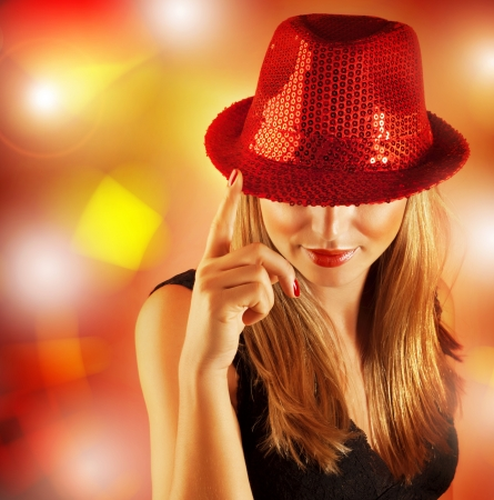 Picture of beautiful woman wearing red hat covered shiny rhinestones and singing on stage in fashionable nightclub, blond girl posing on colorful glowing background, Christmas party photo