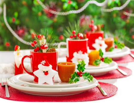 Photo of Christmas table decoration, festive dinnerware with candles and red cups for tea in decorated dinner room, luxury utensil, New Year party, Christmastime table setting, xmas decor Stock Photo