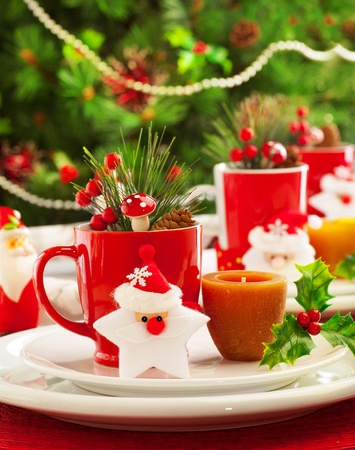 Image of Christmas table decoration, luxury festive utensil over green fir tree background, little red berry twig and star toy decorated table setting in New Year eve, x-mas holiday banquet photo