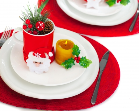Photo of beautiful Christmastime table setting, holiday banquet, christmas celebration, luxury white porcelain dishware on red festive tablecloth, candle and little toys decorated utensil for dinner   photo