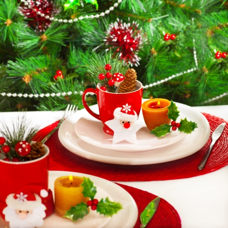 Photo of New Year event banquet, beautiful white plates with Cristmas decoration on holiday setting table, decorated evergreen tree at home in xmas eve, christmastime ornament photo