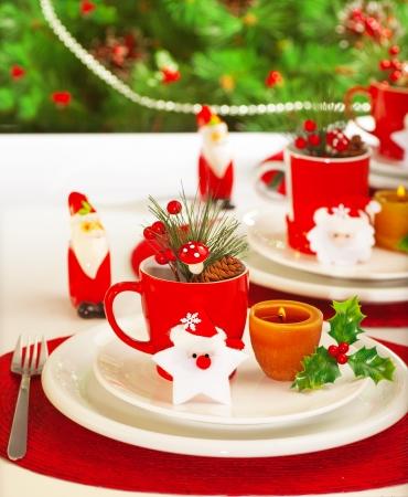 santa cena: Imagen del ajuste de la tabla para las vacaciones de invierno el tiempo, banquete de fiesta, celebración Navidad, vajilla de porcelana de lujo blanco sobre mantel rojo festivo, fiesta año nuevo, decorado árbol de hoja perenne Foto de archivo