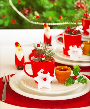 Picture of table setting for winter holidays time, holiday banquet, Christmas celebration, luxury white porcelain dishware on red festive tablecloth, New Year party, decorated evergreen tree photo