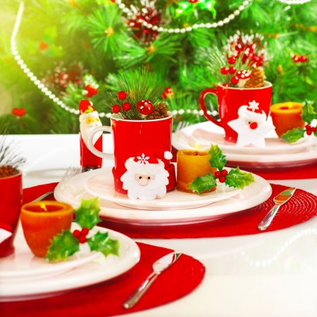 christmas tea: Photo of beautiful Christmas table setting, New Year banquet, adorned evergreen tree, warm yellow sun light in dinning room, luxury porcelain dishware with red festive cup for tea, holiday decoration