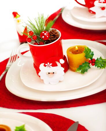 dinnerware: Photo of beautiful Christmastime table setting, holiday banquet, christmas celebration, luxury white porcelain dishware on red festive tablecloth, candle and little toys decorated utensil for dinner