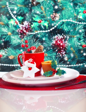 candle light dinner: Image of Christmas eve table decoration, Christmastime still life over gorgeous decorated Christmas tree background, luxury festive red and white dinnerware, New Year party, winter holidays Stock Photo