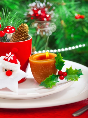 Image of romantic Christmastime dinner with warm candle light, red coffee cup decorated with Santa Claus star and fir cone, beautiful white dinnerware on Christmas tree background, New Year party  photo