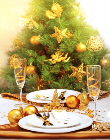 Photo of romantic Christmastime dinner, luxury New Year table setting, gorgeous decorated Christmas tree by golden toys of stars, bubbles and angel, two glass for champagne, holiday still life photo