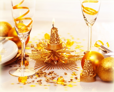 adorned: Photo of romantic Christmas dinner, two glasses for champagne adorned with golden ribbon, beautiful little candle, gold shiny bauble, holiday table setting, New Year decorations