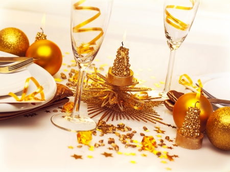 Picture of Christmas romantic table setting, two glasses for champagne adorned with golden ribbon, beautiful little candle, gold shiny bauble, holiday dinner in restaurant, New Year party photo