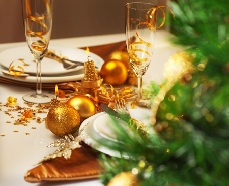 Photo of luxury Christmastime table setting, holiday dinner in restaurant, festive white dinnerware decorated with pretty golden balls and ribbons, warm candle light, green Christmas tree in room photo