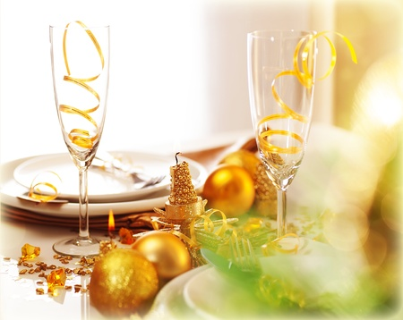 Image of beautiful decorated New Year table setting, romantic holiday dinner in restaurant, golden Christmas decorations, white plates served with silver cutlery and glasses for wine, fir twig