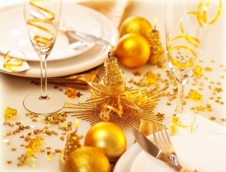 Image of Christmastime table decoration, luxury white dishware served with silver cutlery adorned with glowing glitters, golden holiday decorations, festive utensil, romance New Year dinner photo