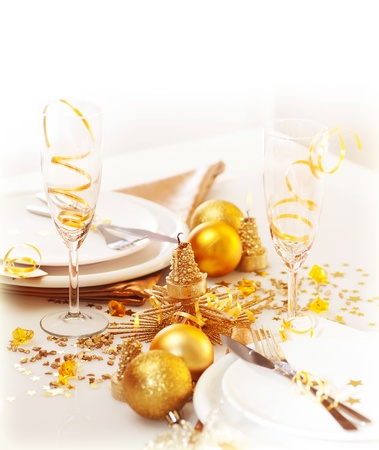 dinnerware:  Photo of xmas holiday table setting, closeup festive dinnerware still life, two glasses for champagne, traditional New Year alcohol beverage, luxury white plate decorated with golden bubble toy