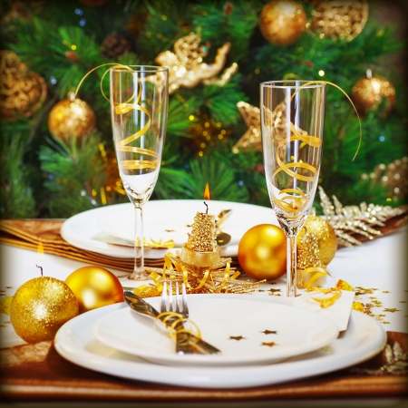 Image of Christmas dinner in restaurant, Christmastime table setting over decorated fir tree background, white plates served with knife and fork, two glass for champagne decorated with golden ribbon  photo