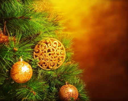 Photo of traditional Christmas tree isolated on brown grunge background, green fir decorated with golden bubbles toy, happy New Year greeting card, adorned pine tree at home, winter holidays photo