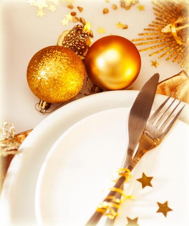 dining set: Image of luxury Christmas table setting, festive white dishware served with silver cutlery and decorated with beautiful golden candle and shiny bauble, New Year holiday, xmas celebration