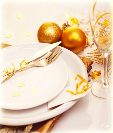 Photo of luxury Christmas table decoration, white plate with knife and fork, glass for wine, traditional New Year holiday table setting with golden bubble decor, happy Christmastime celebration photo