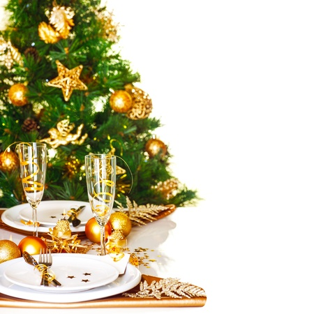 dinnerware: Photo of Christmastime table setting border, beautiful decorated Christmas tree isolated on white background, romantic holiday dinner, luxury white dishware decorated with golden ribbon