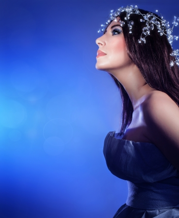 Photo of snow queen, attractive woman with festive diamond jewelery on head isolated on blue background, side view of stylish female wearing luxury shiny accessories on dark brown hair, Christmas eve photo