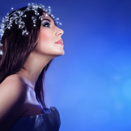 Picture of gorgeous woman isolated on blue background, closeup portrait of pretty brunet girl wearing festive jewelery, sexy female with stylish makeup and luxury accessories on head, New Year party photo