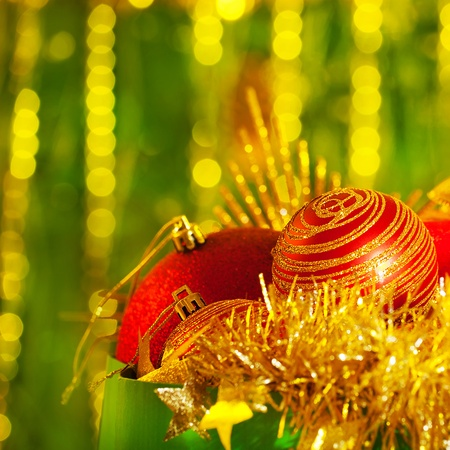 Imagen de la decoraci�n para el �rbol de Navidad en bolsa de papel verde sobre fondo brillante, chucher�a roja diferente y guirnalda de oro, tarjeta de felicitaci�n festiva, felices fiestas de A�o Nuevo, ornamento de lujo Foto de archivo - 16510494