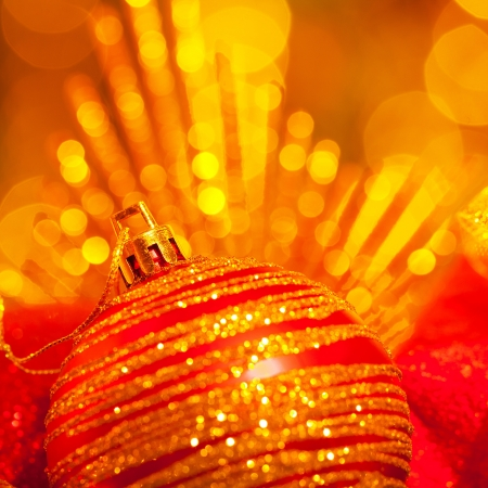 Image of shiny Christmas tree decoration, beautiful red bubble on glowing yellow lights background, New Year greeting card, happy holiday concept, festive garland glitters, x-mas ornament still life  photo