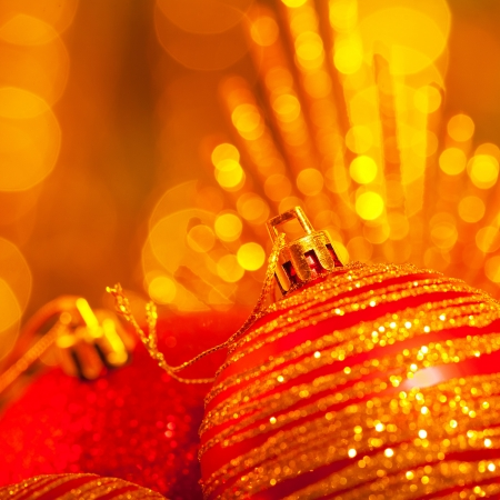 shallow focus: Photo of New Year holiday decoration on golden festive background, red bubble toy for Christmas tree, Christmastime still life, beautiful holiday greeting card, traditional wintertime decor